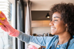 afro-woman-cleaning-window-with-rag-at-home_58466-10801