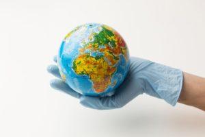 vue-face-main-gants-tenant-globe-terrestre_23-2148630408