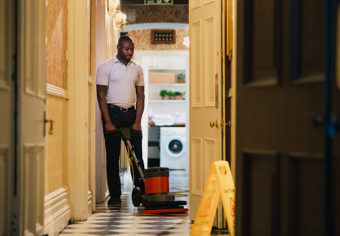 A man is using a machine to polish the corridors in the hotel where he works.