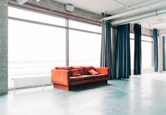 Orange cushion and sofa against large window. Seating furniture at entrance hall. Interior of bright hostel.